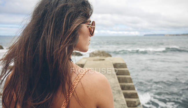 Woman with long brown hair standing on pier looking at distance — Stock Photo
