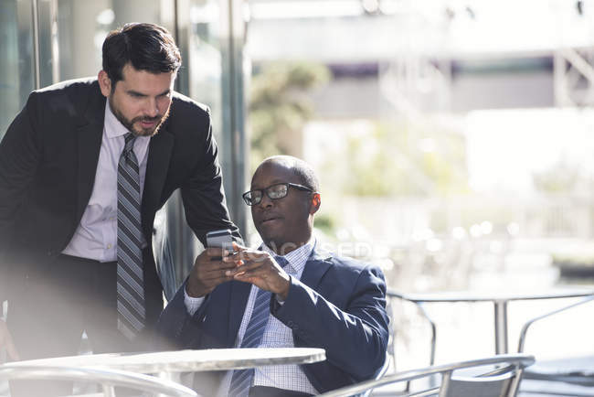 Two businessmen sharing cell phone at outdoor cafe — Stock Photo