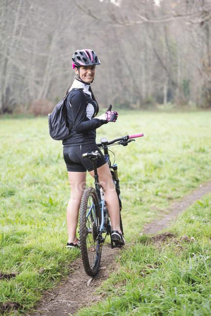 Жінка, стоячи з гірський велосипед — стокове фото