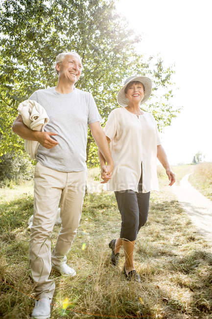 Senior couple walking outdoors in sunny nature — Stock Photo