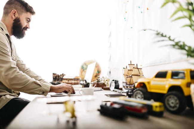 Людина, що сидить на своєму столі з автомобіля і поїздів іграшку в Архітекторі моделі ноутбука — стокове фото