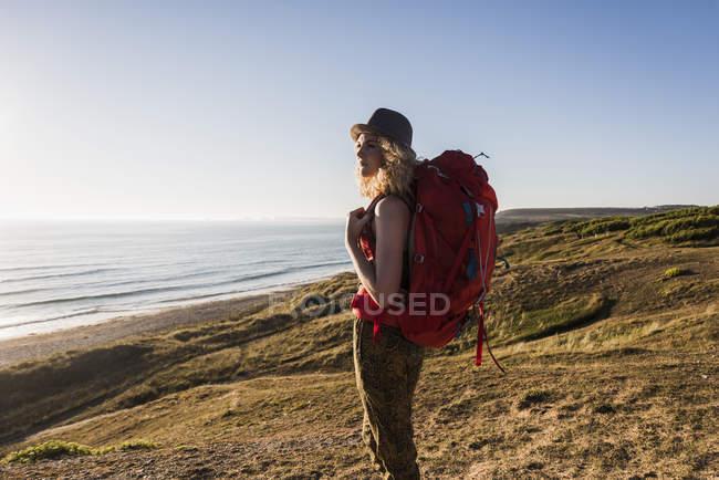 Adolescente com mochila à beira-mar olhando para a distância no crepúsculo da noite — Fotografia de Stock