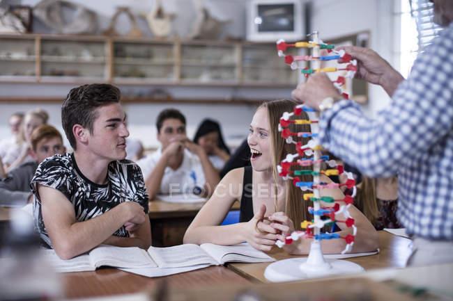 Professor com modelo de DNA e alunos em sala de aula — Fotografia de Stock