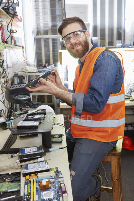Worker dismantling hard disk in computer recycling plant — Stock Photo