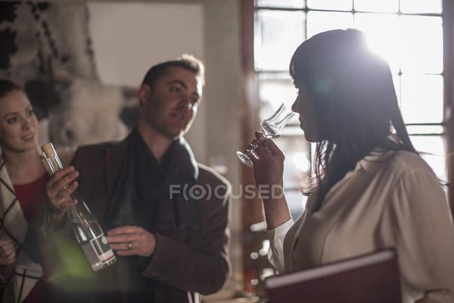 Женщина, дегустация вина в ресторане и человек бутылка Холдинг — стоковое фото