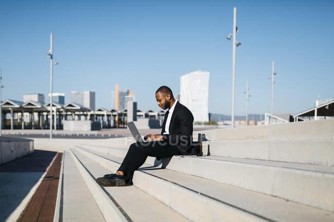 Uomo d'affari seduto sulle scale con bottiglia di birra — Foto stock
