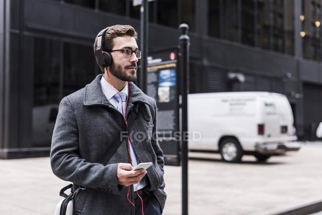 Empresário caminhando com celular — Fotografia de Stock
