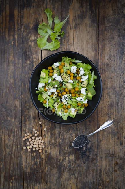 Schüssel mit Blattsalat mit gerösteten Kichererbsen, Avocado, Schafskäse und schwarzem Sesam — Stockfoto