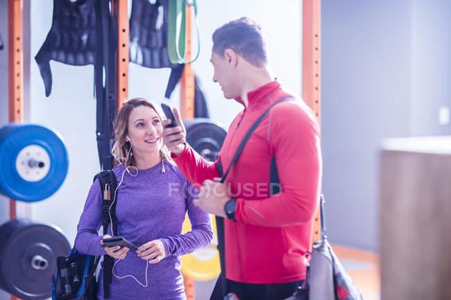 Молодий чоловік і жінка з стільникових телефонів і навушники в тренажерному залі — стокове фото