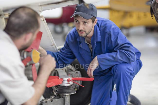 Mechanics repairing light aircraft fans — Stock Photo