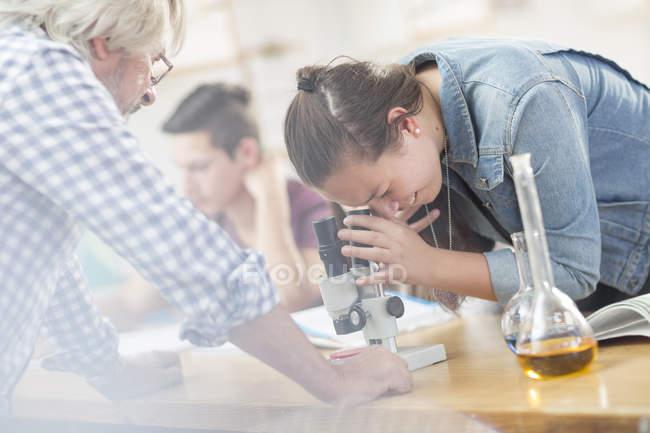 Étudiant de la science avec un enseignant en classe en regardant à travers le microscope — Photo de stock