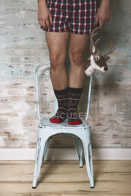Uomo in piedi su sedia tiene testa artificiale dei cervi — Foto stock
