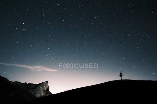 Silhueta de Áustria, Mondsee, de mulher em pé sob o céu estrelado — Fotografia de Stock