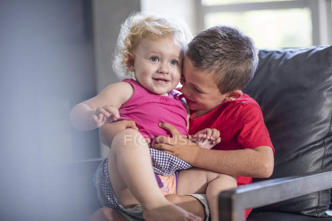 Brother and baby girl on couch,having fun — Stock Photo