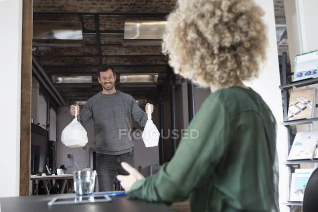 Homem trazendo comida para viagem no escritório moderno — Fotografia de Stock