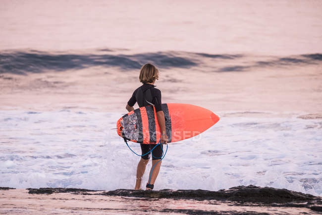 Rear view of teenager boy standing with surfboard on the beach — Stock Photo