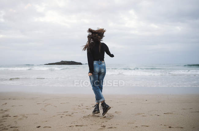 Back view of young woman jumping on the beach — Stock Photo