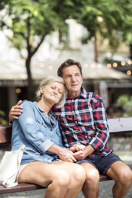 Щаслива пара старший, обіймати один одного на лавці в парку — стокове фото