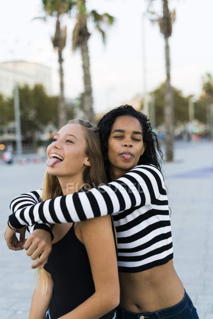 Two playful young women hugging on square — Stock Photo