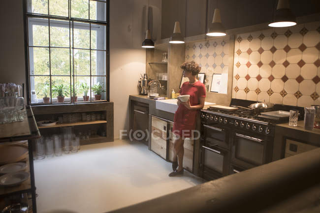 Young woman standing in the kitchen and looking through window — Stock Photo