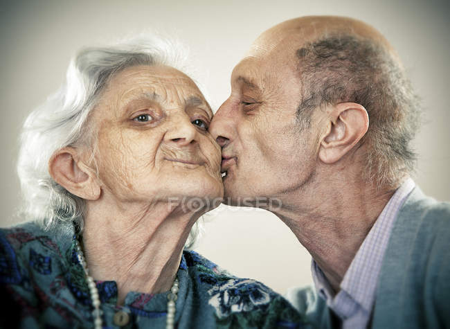 Portrait of senior man kissing smiling woman — Stock Photo