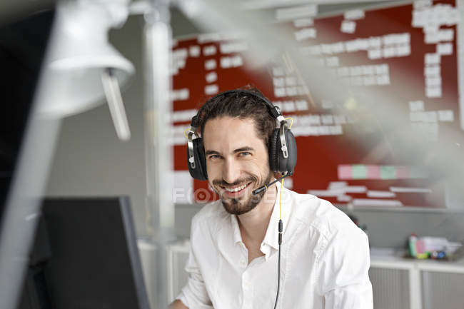 Smiling caucasian businessman in modern office — Stock Photo
