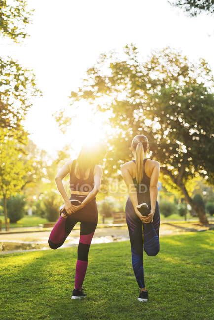 Dos jóvenes que se estiran en el parque al atardecer - foto de stock