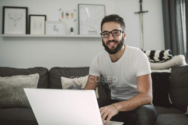 Casual young man using a laptop at home — Stock Photo
