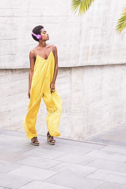 Jeune fille américaine africaine attrayante en robe jaune écoutant de la musique dans les écouteurs — Photo de stock