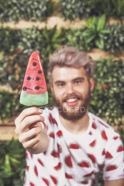 Close-up of Young man offering watermelon ice lolly — Stock Photo
