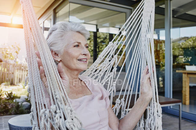 Senior woman sitting in hammock on terrace — Stock Photo