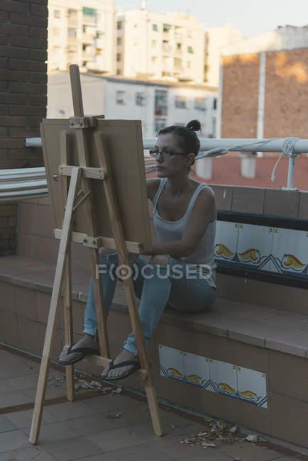 Junge Frau zeichnet auf Dachterrasse ihres Penthouses — Stockfoto