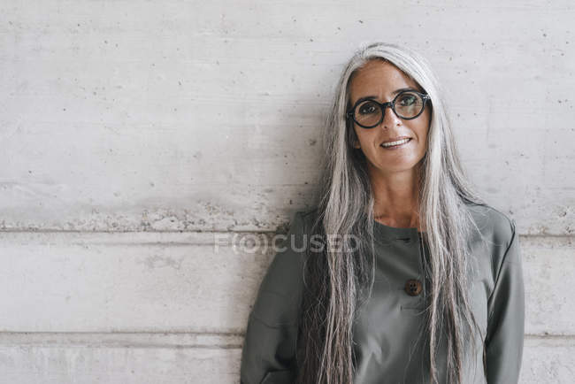 Portrait of smiling woman with long grey hair leaning against wall — Stock Photo