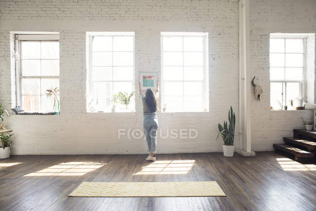Giovane donna allegare cornice al muro di mattoni in un loft — Foto stock