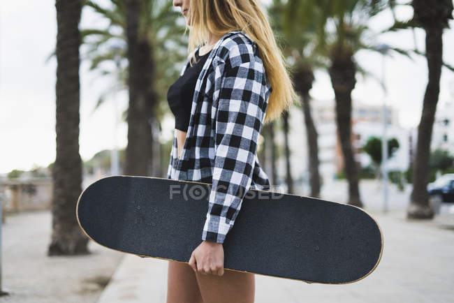 Young woman with skateboard standing on waterfront promenade — Stock Photo