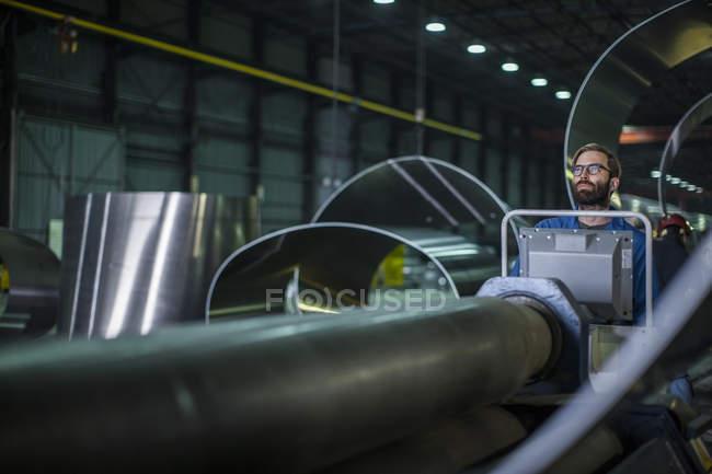 Uomo che fa funzionare i macchinari al pannello di controllo in fabbrica di cisterna — Foto stock