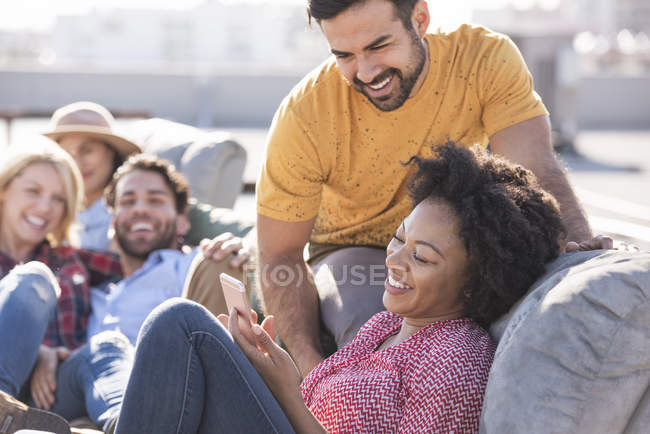 Friends at rooftop party, young woman holding smartphone — Stock Photo