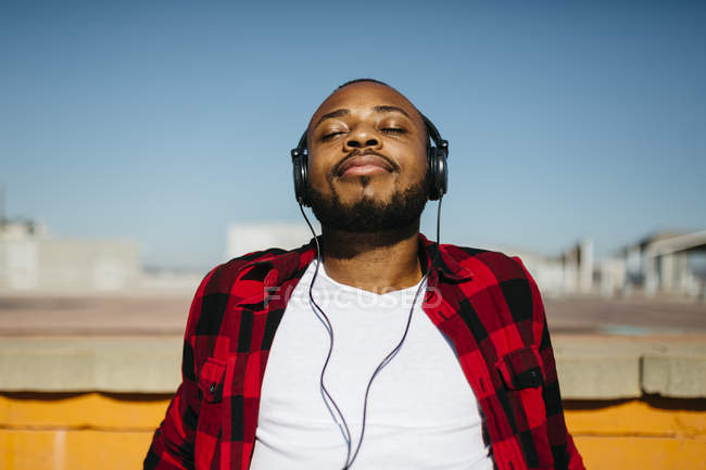 Man listening to music with headphones outdoors — Stock Photo
