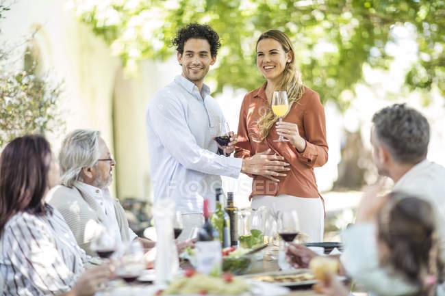 Jeune couple lever un toast avec l'annonce de la grossesse à la famille pendant le déjeuner familial extérieur — Photo de stock