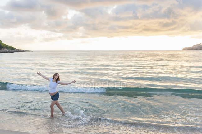 Happy pregnant woman dancing on beach — Stock Photo