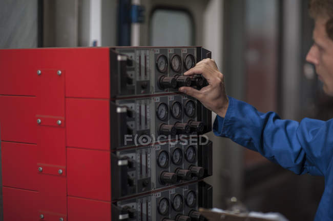Close-up of worker operating control panel in factory — Stock Photo