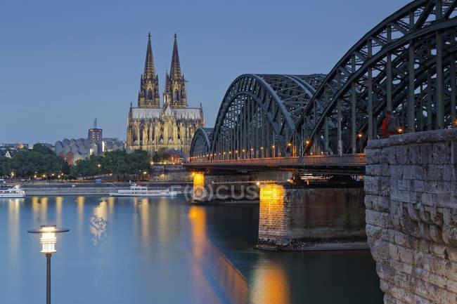 Alemania, Colonia, la Catedral de Colonia iluminada y el hombre sentado en el puente de Hohenzollern - foto de stock