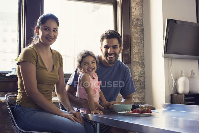 Happy family sitting in kitchen and looking at camera — Stock Photo