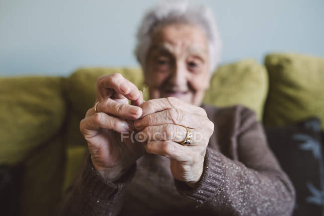 Close-up of senior woman passing thread through buttonhole of sewing needle — Stock Photo