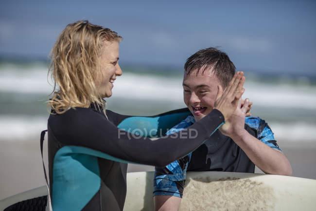 Adolescent heureux avec le syndrome de down et de la femme avec planche de surf sur la plage — Photo de stock