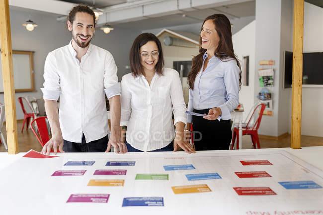 Trois collègues heureux dans le bureau moderne — Photo de stock