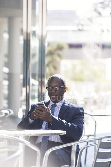 Бизнесмен, используя мобильный телефон в открытом кафе — стоковое фото