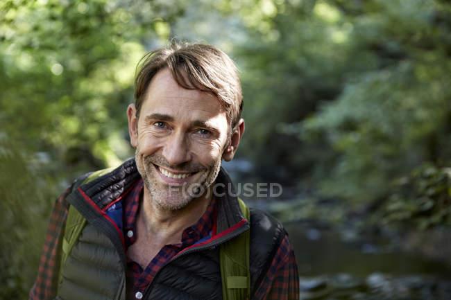 Sorrindo Caminhante olhando para a câmera na floresta — Fotografia de Stock