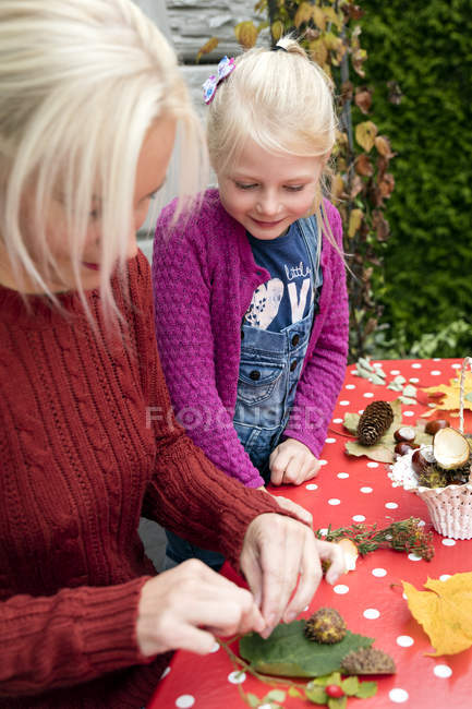 Little girl watching her mother tinkering autumnal decoration — Stock Photo