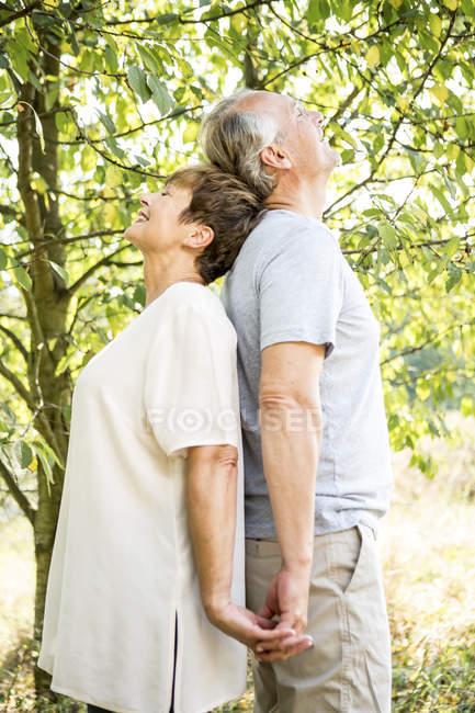 Старшая пара стоит спиной к спине в зеленом саду — стоковое фото